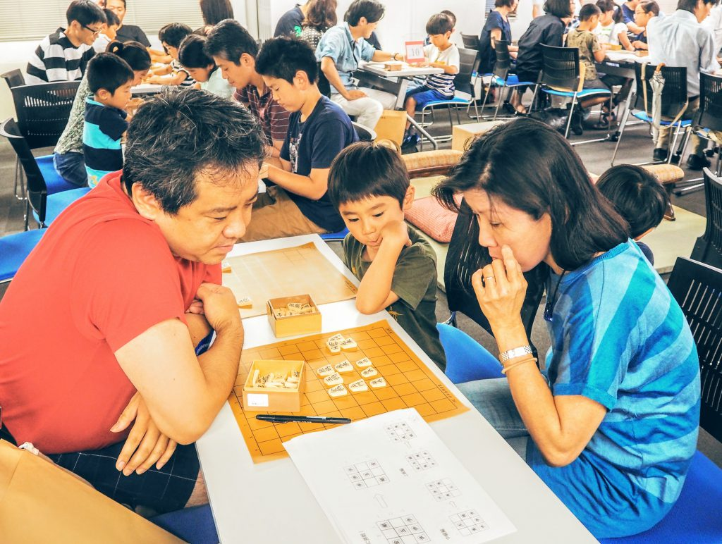Parents and children are solving puzzles together.